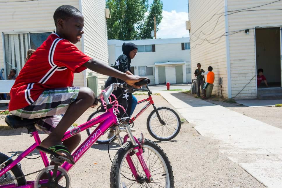 Chris Detrick  |  The Salt Lake Tribune Innocent Byiringiro, 11, and Asma Ali, 11, ride bikes at the Hser Ner Moo Community Center in South Salt Lake on Tuesday, July 18, 2017.