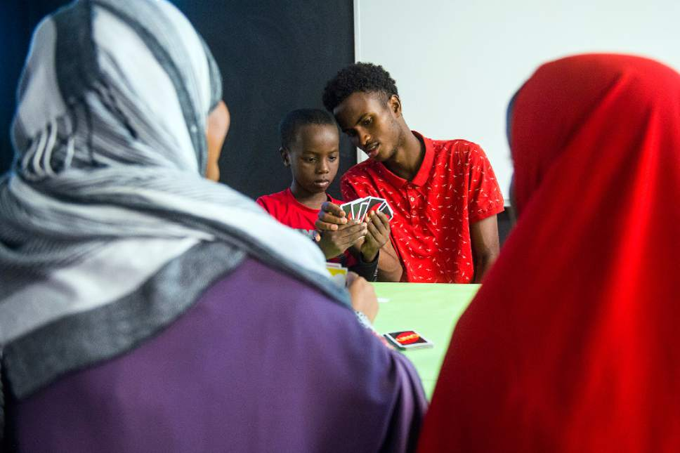 Chris Detrick  |  The Salt Lake Tribune Promise Prevention Specialist Said Mohamed plays cards with Abdi Mahad, 7, at the Hser Ner Moo Community Center in South Salt Lake on Tuesday, July 18, 2017.