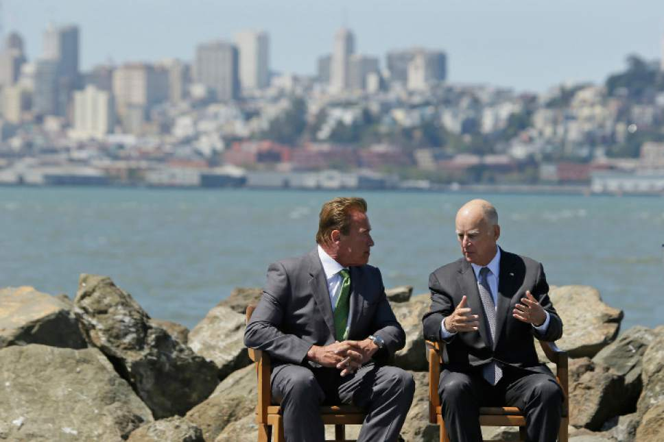 California Gov. Jerry Brown, right, and former Gov. Arnold Schwarzenegger, left, talk before a climate bill signing on Treasure Island, Tuesday, July 25, 2017, in San Francisco. Gov. Jerry Brown signed legislation Tuesday keeping alive California's signature initiative to fight global warming, which puts a cap and a price on climate-changing emissions. The Democratic governor was joined by his celebrity predecessor, Arnold Schwarzenegger, who signed the 2006 bill that led to the creation of the nation's only cap and trade system to reduce greenhouse gases in all industries. (AP Photo/Eric Risberg)