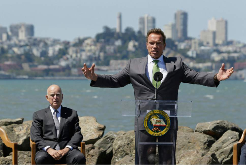 Former California Gov. Arnold Schwarzenegger gestures while speaking as Gov. Jerry Brown, left, listens before a climate bill signing on Treasure Island, Tuesday, July 25, 2017, in San Francisco. Gov. Jerry Brown signed legislation Tuesday keeping alive California's signature initiative to fight global warming, which puts a cap and a price on climate-changing emissions. The Democratic governor was joined by his celebrity predecessor, Arnold Schwarzenegger, who signed the 2006 bill that led to the creation of the nation's only cap and trade system to reduce greenhouse gases in all industries.(AP Photo/Eric Risberg)