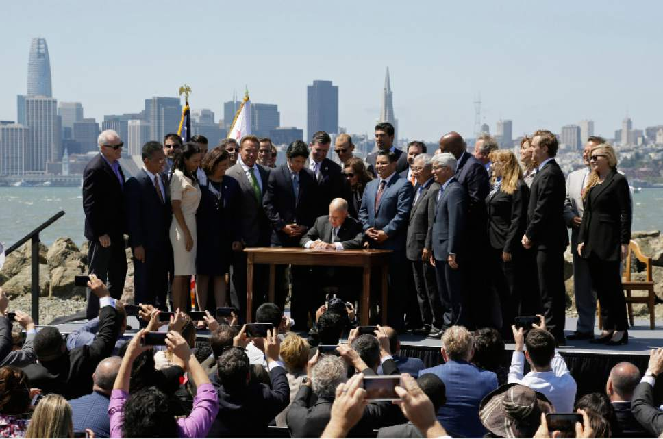 California Gov. Jerry Brown signs a climate bill as former Gov. Arnold Schwarzenegger, fifth from left, watches on Treasure Island, Tuesday, July 25, 2017, in San Francisco. Gov. Jerry Brown signed legislation Tuesday keeping alive California's signature initiative to fight global warming, which puts a cap and a price on climate-changing emissions. The Democratic governor was joined by his celebrity predecessor, Arnold Schwarzenegger, who signed the 2006 bill that led to the creation of the nation's only cap and trade system to reduce greenhouse gases in all industries. (AP Photo/Eric Risberg)