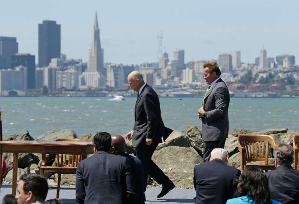 California Gov. Jerry Brown, left, walks to sign a climate bill and is followed by former Gov. Arnold Schwarzenegger, right, on Treasure Island, Tuesday, July 25, 2017, in San Francisco. Gov. Jerry Brown signed legislation Tuesday keeping alive California's signature initiative to fight global warming, which puts a cap and a price on climate-changing emissions. The Democratic governor was joined by his celebrity predecessor, Arnold Schwarzenegger, who signed the 2006 bill that led to the creation of the nation's only cap and trade system to reduce greenhouse gases in all industries. (AP Photo/Eric Risberg)
