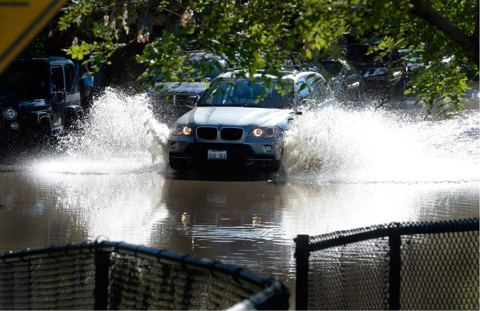 Scott Sommerdorf   |  The Salt Lake Tribune   A determined motorist plowed through flooded Lucy Street to get to northbound 200W. Northbound Main Line TRAX trains were prevented from leaving the Ballpark TRAX station due to flooding, Wednesday, July 26, 2017.