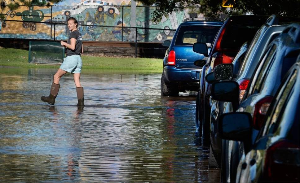 Scott Sommerdorf   |  The Salt Lake Tribune   A Lucy Street resident got out into the flooded street in her boots to examine the flooded street. Northbound Main Line TRAX trains were prevented from leaving the Ballpark TRAX station due to flooding, Wednesday, July 26, 2017.