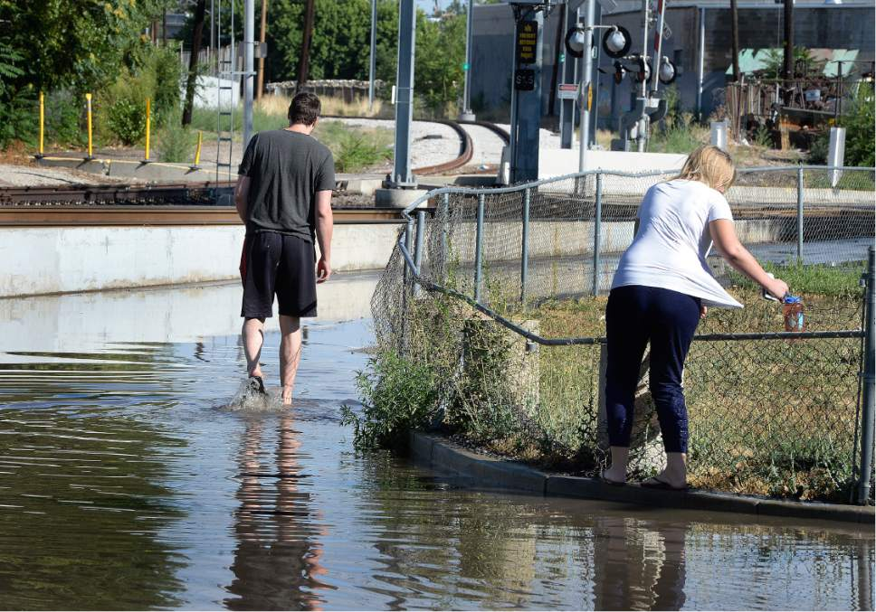 Scott Sommerdorf   |  The Salt Lake Tribune   Lucy Street residents got out into the flooded street to try and walk around the corner to 200W. Northbound Main Line TRAX trains were prevented from leaving the Ballpark TRAX station due to flooding, Wednesday, July 26, 2017.