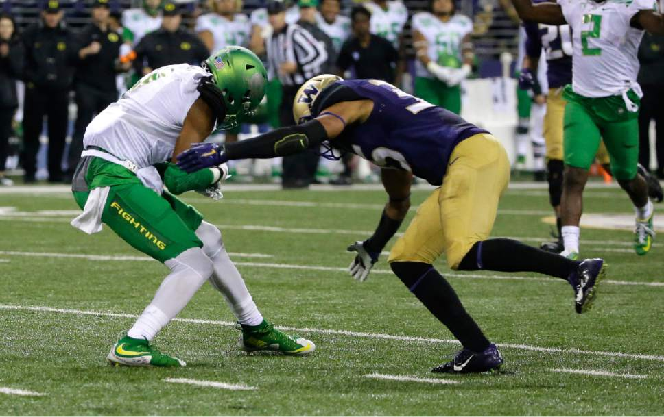 Washington defensive back Brian Clay, right, prepares to tackle Oregon wide receiver Darren Carrington during the second half of an NCAA college football game, Saturday, Oct. 17, 2015, in Seattle. Clay was ejected from the game for targeting on the play. Oregon won 26-20. (AP Photo/Ted S. Warren)
