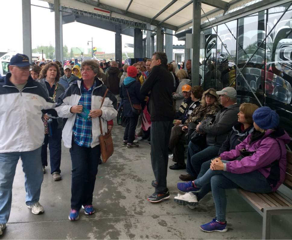 Passengers from the Emerald Princess cruise ship wait on shore for excursions to explore the Juneau, Alaska area, Wednesday, July 26, 2017. The passengers were allowed off the ship late Wednesday afternoon. The FBI is investigating the domestic dispute death of a Utah woman on board the ship, which had been traveling in U.S. waters outside Alaska. (AP Photo/Becky Bohrer)