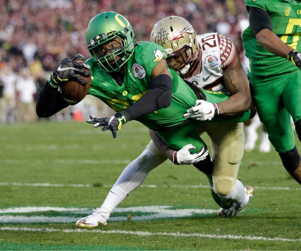 Oregon wide receiver Darren Carrington, front, scores under pressure by Florida State defensive back Trey Marshall during the second half of the Rose Bowl NCAA college football playoff semifinal, Thursday, Jan. 1, 2015, in Pasadena, Calif. (AP Photo/Jae C. Hong)