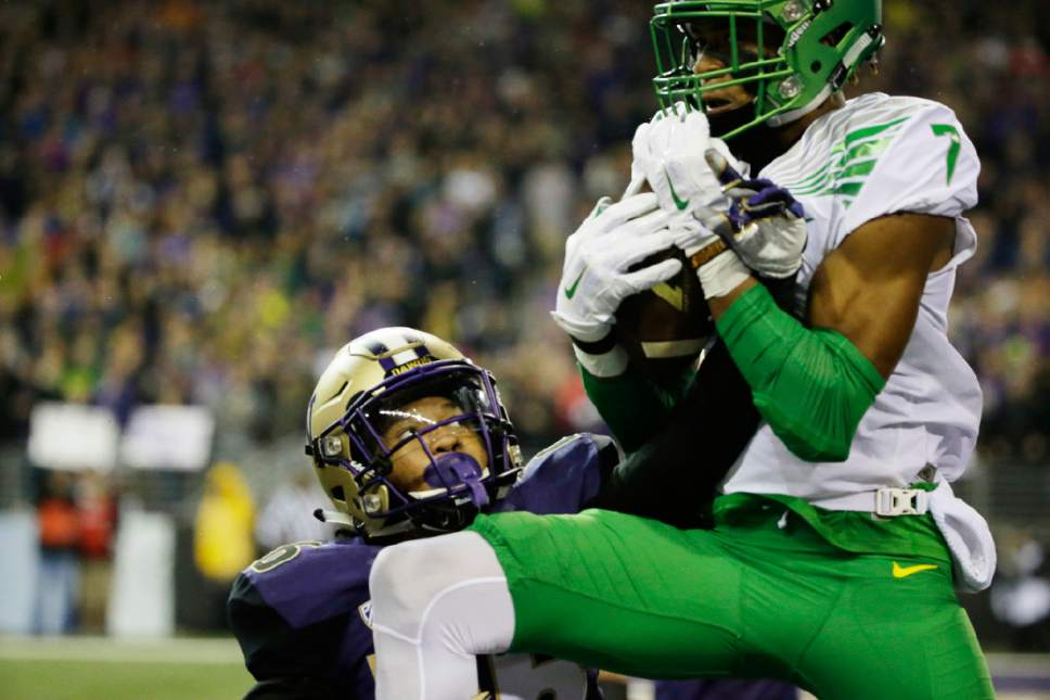 Oregon wide receiver Darren Carrington, right, comes down with a touchdown catch over the defense of Washington defensive back Sidney Jones, left, in the first half of an NCAA college football game, Saturday, Oct. 17, 2015, in Seattle. (AP Photo/Ted S. Warren)