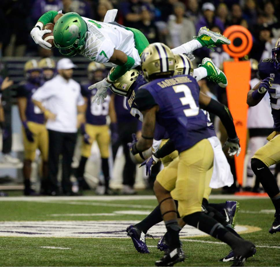 Oregon wide receiver Darren Carrington (7) leaps over Washington defensive back Budda Baker as Washington's Darren Gardenhire (3) watches during the second half of an NCAA college football game, Saturday, Oct. 17, 2015, in Seattle. Oregon won 26-20. (AP Photo/Ted S. Warren)