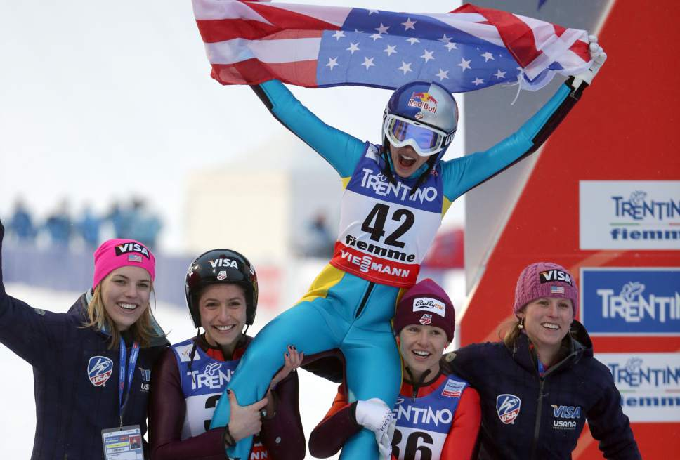 Sarah Hendrickson of the United States celebrates with teammates after winning the women's ski jumping HS 106 Individual at the Nordic Ski World Championships in Val di Fiemme, Italy, Friday, Feb. 22, 2013.  (AP Photo/Matthias Schrader)