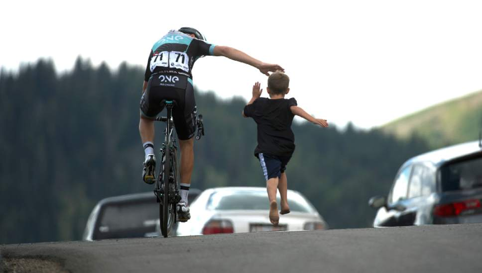 Leah Hogsten  |  The Salt Lake Tribune Dion Smith with One Pro Cycling gets a high-five from Cache Cragan, 8, of Logan who ran beside him on Guardsman's Pass during Stage 6 of the Tour of Utah on Saturday, August 6, 2016 that took cyclists on a 114-mile ride with over 11,000 feet of climbing from Snowbasin Ski Resort to Snowbird.