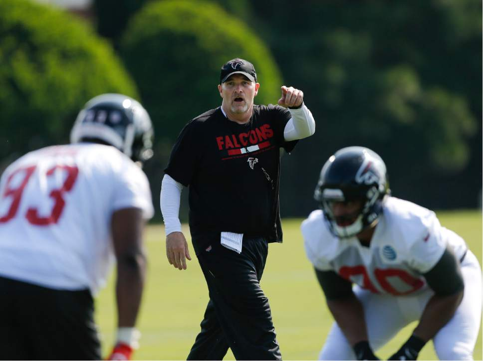 Atlanta Falcons head coach Dan Quinn works with his players during NFL football training camp Thursday, July 27, 2017, in Flowery Branch, Ga. (AP Photo/John Bazemore)