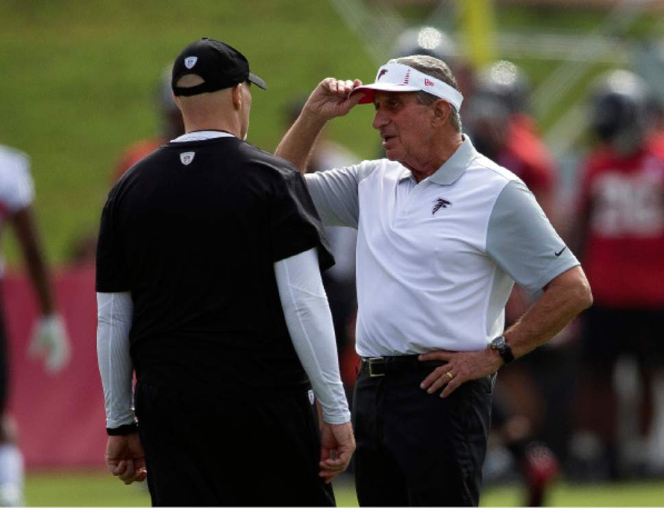 Atlanta Falcons owner Arthur Blank, right, talks with head coach Dan Quinn during NFL football training camp Friday, July 28, 2017, in Flowery Branch, Ga. (AP Photo/John Bazemore)