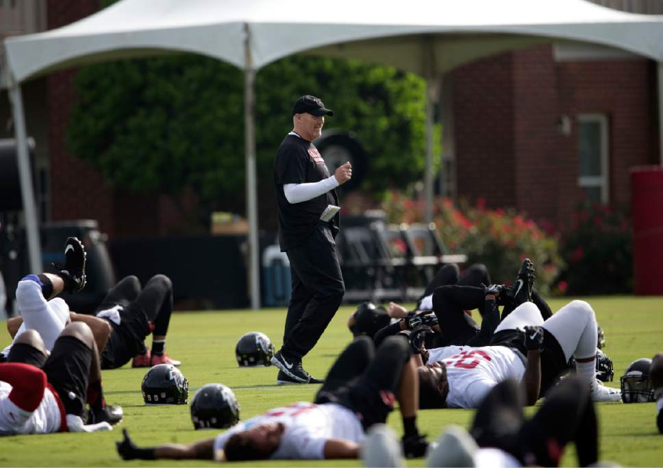 Atlanta Falcons head coach Dan Quinn walks among his players as they stretch during NFL football training camp Friday, July 28, 2017, in Flowery Branch, Ga. (AP Photo/John Bazemore)
