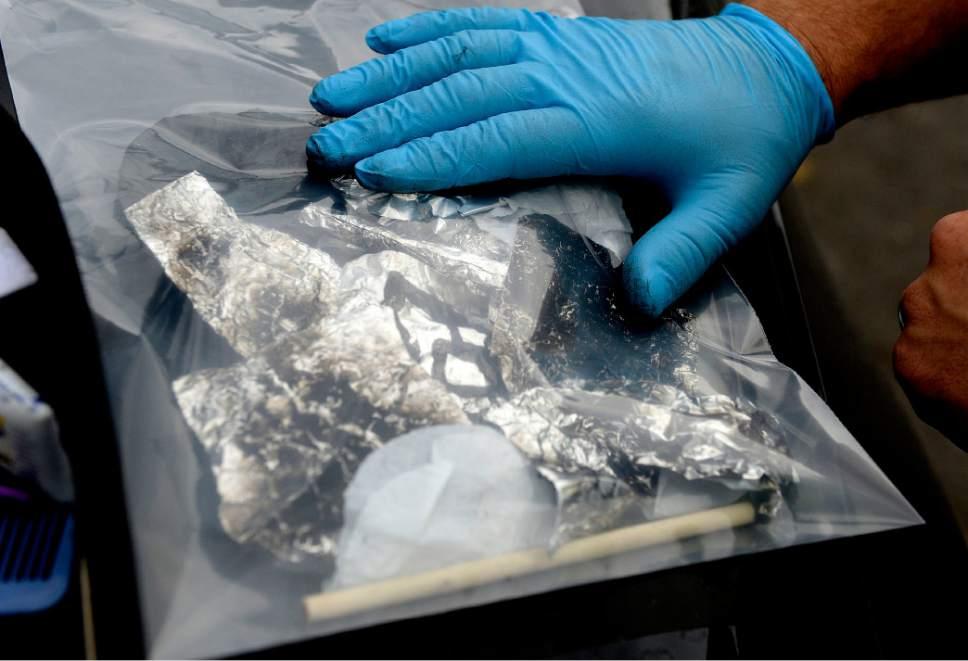 Al Hartmann  |  The Salt Lake Tribune Salt Lake City police officer bags up tinfoil used to inhale burning heroin after a drug bust in the Rio Grande neighborhood Wednesday July 19.