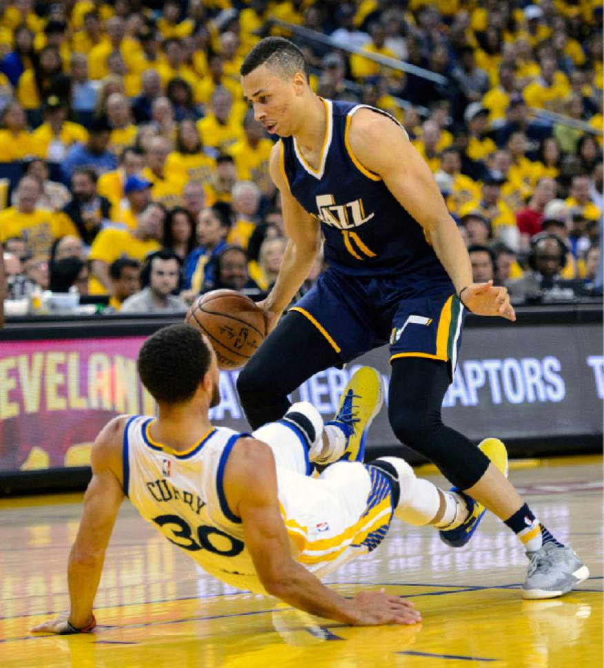 Steve Griffin  |  The Salt Lake Tribune   Utah Jazz guard Dante Exum (11) draws a charging foul as he knocks down Golden State Warriors guard Stephen Curry (30) during game 2 of the NBA playoff game between the Utah Jazz and the Golden State Warriors at Oracle Arena in Oakland Thursday May 4, 2017.