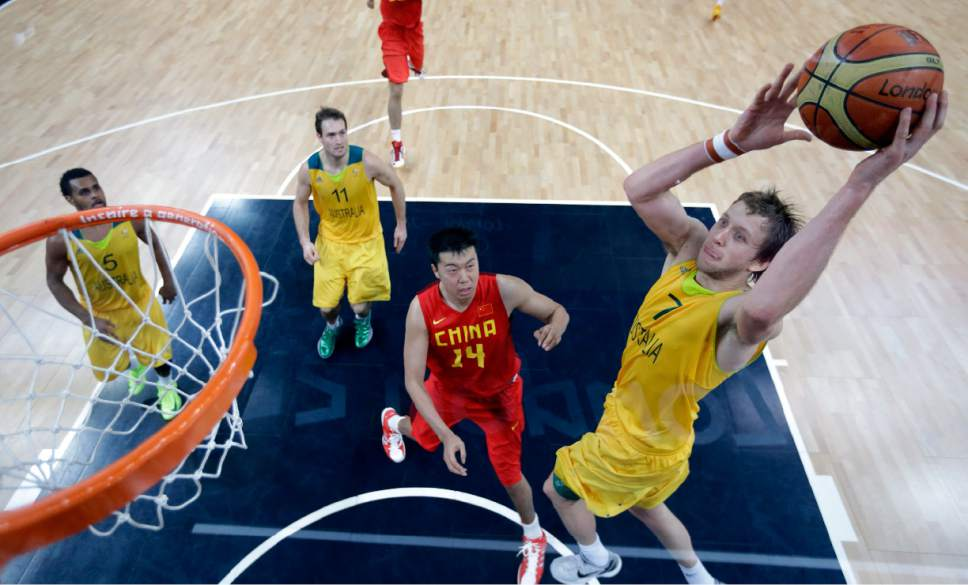 Australia's Joe Ingles (7) goes over China defender  Wang Zhizhi during a men's basketball game at the 2012 Summer Olympics, Thursday, Aug. 2, 2012, in London. (AP Photo/Eric Gay, pool)