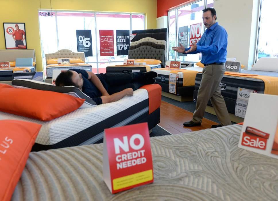 Al Hartmann   The Salt LakeTribune Assistant Manager Rory Snyder Shows A  Shopper Mattress Options In