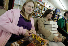 Jim Urquhart  |  The Salt Lake TribuneProvo residents and sisters Pamela Dorsey, left, and Kathleen Dorsey holds stacks of books as sci-fi author and BYU professor Brandon Sanderson reads from his book