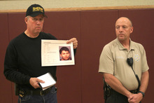 Jim Driscoll, Chief Deputy for Coconino County Arizona,  holds a photo of Suspect Scott Curley, at a press conference at an LDS church in Fredonia, at 1 a.m. Friday.  Kane County Sgt. Alan Alldredge is on the right. (Rick Egan/The Salt Lake Tribune)
