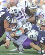 BYU's Brandon Ogletree (left) and other BYU players tackle Washington's quarterback Jake Locker (10) during an NCAA college football game at LaVell Edwards Stadium in Provo, Utah, Saturday, Sept. 4, 2010. (AP Photo/George Frey)