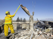 Al Hartmann  |  The Salt Lake Tribune Engineer Fenton Quinn of the Unified Fire Deptartment pulls down an unstable chimney from the Burnses' destroyed home in Herriman on Monday afternoon.