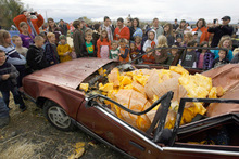 Francisco Kjolseth  |  The Salt Lake TribuneThe year's state record pumpkin of 1,169 pounds fills a car Oct. 23 after being dropped from a 175-foot crane at Hee Haw Farms in Pleasant Grove, completely destroying a Pontiac 6000. The pumpkin was grown by Matt McConkie from Mountain Green and it is calculated that the descent of the giant pumpkin reached a top speed of 67.1mph for 3.1 seconds before meeting its demise.