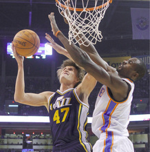 Utah Jazz forward Andrei Kirilenko, left, of Russia, goes up for a shot while defended by Oklahoma City Thunder forward Serge Ibaka, right, of the Republic of Congo, in the first quarter of an NBA basketball game in Oklahoma City, Sunday, Oct. 31, 2010. (AP Photo/Sue Ogrocki)
