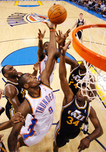 Oklahoma City Thunder forward Serge Ibaka, center, of Republic of Congo, grabs a rebound in front of Utah Jazz forward C.J. Miles, right, and forward Al Jefferson, left, in the second quarter of an NBA basketball game in Oklahoma City, Sunday, Oct. 31, 2010. Utah won 120 -99. (AP Photo/Sue Ogrocki)