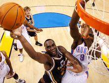 Utah Jazz forward Al Jefferson shoots next to Oklahoma City Thunder forward Serge Ibaka, right, during the third quarter of an NBA basketball game in Oklahoma City, Sunday, Oct. 31, 2010. Jefferson had 23 points as Utah won 120-99. (AP Photo/Sue Ogrocki)