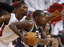 Utah Jazz power forward Paul Millsap, right, drives past Miami Heat power forward Chris Bosh during the first half of an NBA basketball game Tuesday, Nov. 9, 2010 in Miami. (AP Photo/Wilfredo Lee)
