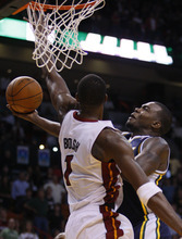 Utah Jazz power forward Paul Millsap goes up for a shot against Miami Heat power forward Chris Bosh (1) during overtime in an NBA basketball game Tuesday, Nov. 9, 2010 in Miami. Millsap scored a career-high 46 points as the Jazz defeated the Heat 116-114 in overtime. (AP Photo/Wilfredo Lee)