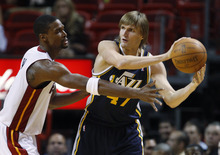 Utah Jazz small forward Andrei Kirilenko attempts to pass past Miami Heat power forward Chris Bosh during the second half of an NBA basketball game,  Tuesday, Nov. 9, 2010 in Miami. The Jazz defeated the Heat 116-114 in overtime. (AP Photo/Wilfredo Lee)
