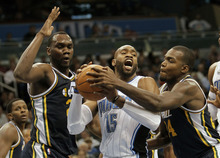 Orlando Magic shooting guard Vince Carter (15) looks for a teammate to pass the ball as he is guarded by Utah Jazz center Al Jefferson, left, and power forward Paul Millsap during the first half of an NBA basketball game in Orlando, Fla., Wednesday, Nov. 10, 2010.(AP Photo/John Raoux)