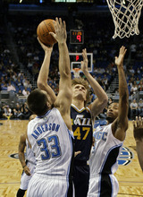 Utah Jazz small forward Andrei Kirilenko (47), of Russia,  goes in for a shot between Orlando Magic power forward Ryan Anderson (33) and power forward Rashard Lewis during the first half of an NBA basketball game in Orlando, Fla., Wednesday, Nov. 10, 2010. (AP Photo/John Raoux)