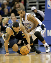 Utah Jazz point guard Deron Williams, left, and Orlando Magic point guard Jameer Nelson (14) scramble for a loose ball during the first half of an NBA basketball game in Orlando, Fla., Wednesday, Nov. 10, 2010.(AP Photo/John Raoux)