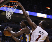 Utah Jazz small forward C.J. Miles goes up for a shot against Miami Heat power forward Chris Bosh (1) during the second half of an NBA basketball game Tuesday, Nov. 9, 2010 in Miami. The Jazz defeated the Heat 116-114 in overtime. (AP Photo/Wilfredo Lee)