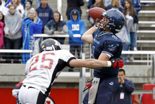 Juan Diego's Nathan Elorreaga makes a pass as he rushed by Hurricane's Josh Bullock during the 3A high school football championships Friday, Nov. 19, 2010, in Salt Lake City. Juan Diego defeated Hurricane for the 3A title 10-7. (Jim Urquhart/ Special to The Salt Lake Tribune)