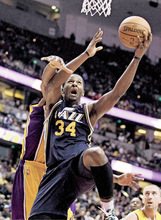Utah Jazz's C.J. Miles goes up for a basket as he is defended by Los Angeles Lakers' Matt Barnes during the first half of an NBA preseason basketball game in Anaheim, Calif., Tuesday, Oct. 19, 2010. (AP Photo/Jae C. Hong)