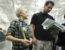 Leah Hogsten  |  The Salt Lake Tribune Andre Holewinski, 11, (left) and his father Robert Holewinski of Eagle Mountain were near the front of the line to meet former President George W. Bush at a book-signing Friday at Costco in Sandy. Holewinski served three tours in Iraq.