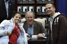 Leah Hogsten  |  The Salt Lake Tribune An unidentified couple share a light moment with former President George W. Bush on Friday as he signed copies of his new memoir at Costco in Sandy.