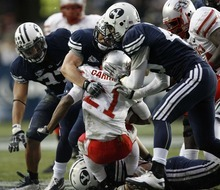 Trent Nelson  |  The Salt Lake Tribune BYU defensive lineman Vic So'oto (37), BYU defensive back Zeke Mendenhall (30) and BYU linebacker Kyle Van Noy (45) bring down New Mexico's Kasey Carrier during the first half,  BYU vs. New Mexico, Saturday, November 20, 2010.