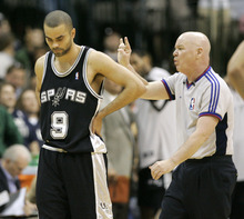 San Antonio Spurs guard Tony Parker (9) of France looks down as NBA referee Joey Crawford makes a call during the second half of their basketball game against the Dallas Mavericks in Dallas, Sunday, April 15, 2007.  Crawford was suspended indefinitely by commissioner David Stern on Tuesday, April 17, 2007 for his conduct toward Spurs player Tim Duncan, who contends the official challenged him to a fight. (AP Photo/Donna McWilliam)