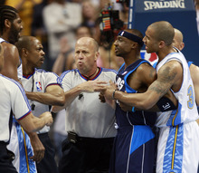Dallas Mavericks guard Jason Terry, second from right is restrained by Denver Nuggets guard Dahntay Jones, right, as Terry exchanges words with Nuggets forward Nene, left, of Brazil, while referees step in to intervene in the first quarter of Game 1 of an NBA basketball Western Conference semifinal in Denver on Sunday, May 3, 2009. Nene and Terry were arguing over a flagrant foul assessed to Nuggets forward Kenyon Martin. (AP Photo/David Zalubowski)