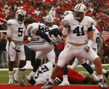 Trent Nelson  |  The Salt Lake Tribune  BYU defensive lineman Matt Putnam (41) and other BYU players celebrate stopping Utah Utes running back Eddie Wide #36 as the Utes face BYU in the first quarter at Rice-Eccles Stadium Saturday, November 27, 2010.