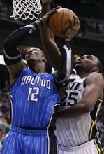 Orlando Magic center Dwight Howard (12) attempts to score as Utah Jazz center Al Jefferson (25) defends during the first half of an NBA basketball game in Salt Lake City, Friday, Dec. 10, 2010. (AP Photo/Colin E Braley)