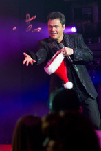 Donny Osmond tosses candy canes to the audience at the curtain call for the opening night performance of 'Donny & Marie - A Broadway Christmas' in New York, Thursday, Dec. 9, 2010. (AP Photo/Charles Sykes)