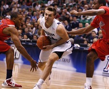 Djamila Grossman  |  The Salt Lake Tribune  Brigham Young University's Kyle Collinsworth, 31, drives the ball toward the basket as the University of Arizona's Kevin Parrom, 3, and Derrick Williams, 23, block him, in a game in Salt Lake City, on Saturday, Dec. 11, 2010. BYU won the game.