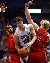 Djamila Grossman  |  The Salt Lake Tribune  Brigham Young University's Jimmer Fredette, 32, falls as he is blocked by the University of Arizona's Kyryl Natyazhko, 1, and Kyle Fogg, 21, during a game in Salt Lake City, on Saturday, Dec. 11, 2010. BYU won the game.